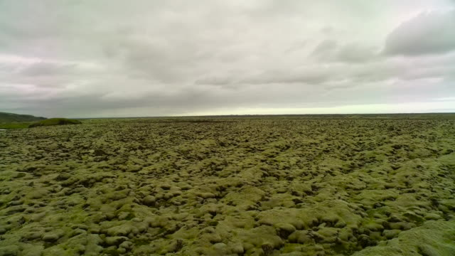 Aerial flying close over moss covered lava rocks in Iceland