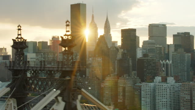 aerial flying close over the 59th street bridge with manhattan in the background with sun setting behind buildings - マンハッタン点の映像素材/bロール