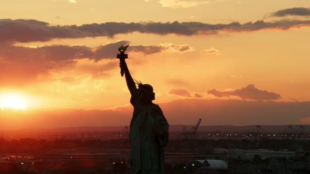 Aerial flying close to Statue of Liberty at sunset