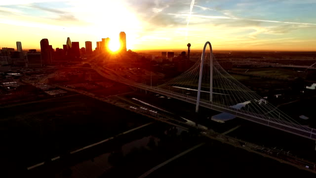 Aerial Flying Closer to the Margaret Hunt Hill Bridge as the Sun rises through Skyscrapers