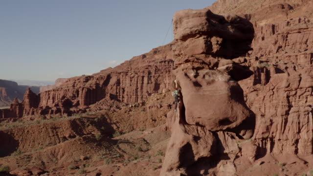 vídeos y material grabado en eventos de stock de aerial flying directly toward female climber ascending rock tower at fisher towers - roca