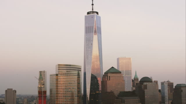 aerial flying down hudson river looing at world trade center in lower manhattan at sunset in nyc - one world trade center stock-videos und b-roll-filmmaterial
