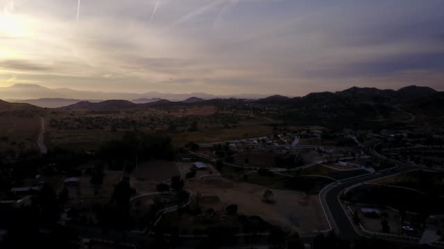 aerial flying down over southern california hilly area at sunrise - riverside california stock videos and b-roll footage
