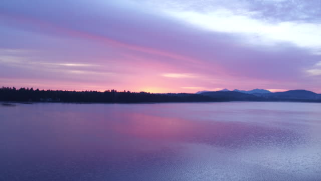 Aerial flying down over water of Saranac lake past small island at Sunrise