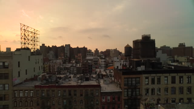 stockvideo's en b-roll-footage met aerial flying east low over buildings at sunrise in manhattan nyc - dak