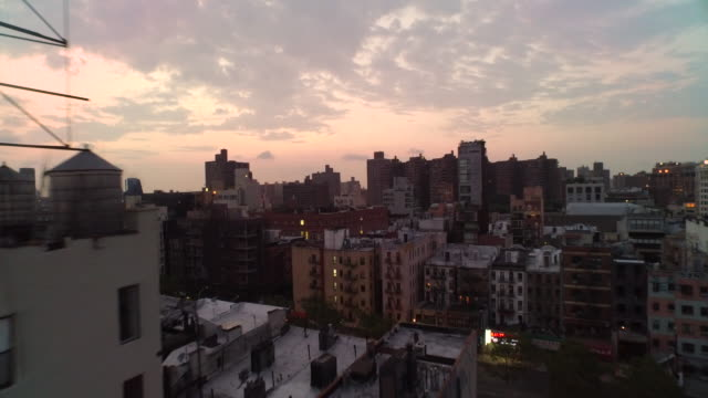 aerial flying east low over buildings past water tower at sunrise in manhattan nyc - brooklyn new york stock videos & royalty-free footage