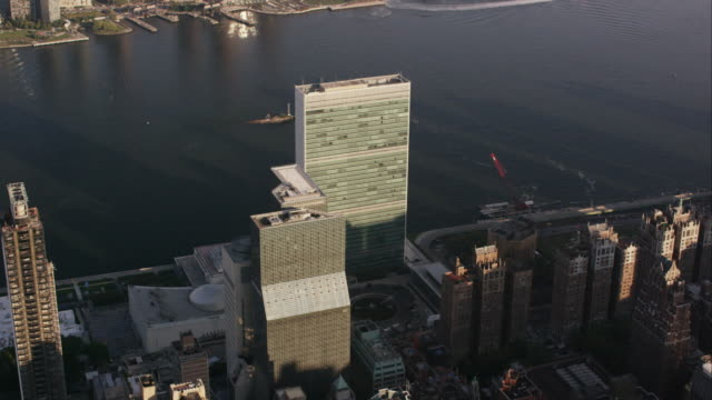 aerial flying east over the un building to the east river, nyc - united nations building stock videos and b-roll footage