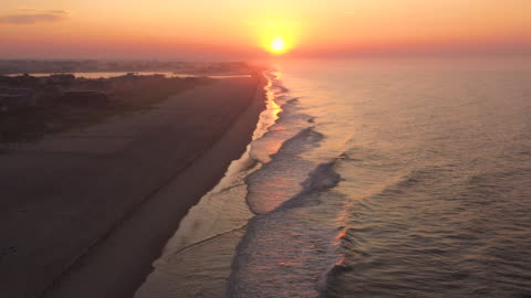 vidéos et rushes de aerial flying forward over beach in bridgehampton, ny at sunrise - long island