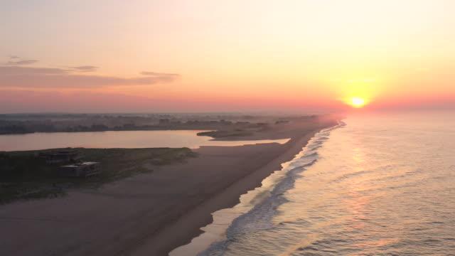 aerial flying forward over beach in bridgehampton, ny at sunrise - bridgehampton stock videos & royalty-free footage
