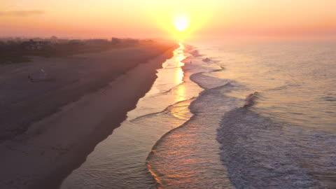 vidéos et rushes de aerial flying forward over beach with man standing in the ocean fishing, bridgehampton, ny at sunrise - long island