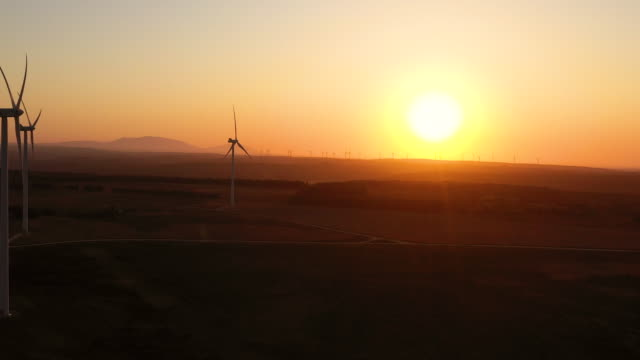 aerial flying forward past a cluster of windmills, wind farm in southern portugal at sunrise - power in nature stock videos & royalty-free footage