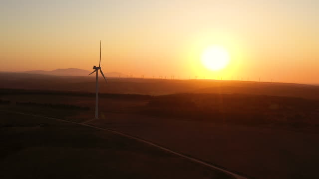 vídeos de stock e filmes b-roll de aerial flying forward past a cluster of windmills, wind farm in southern portugal at sunrise - luz solar
