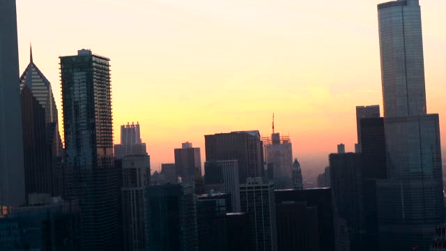 aerial flying high among skyscrapers in chicago at sunset on a winter day - two prudential plaza stock videos & royalty-free footage