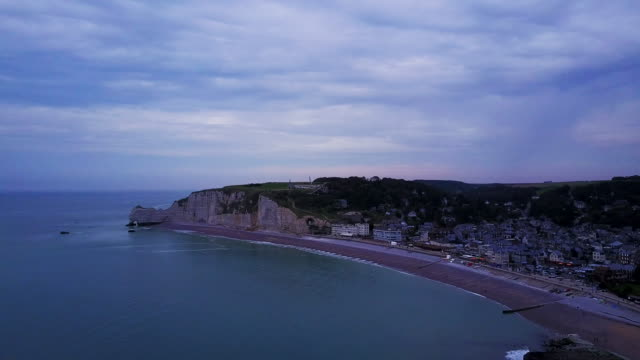 Aerial flying high over the ocean with view of beach and cliffs of Étretat, France