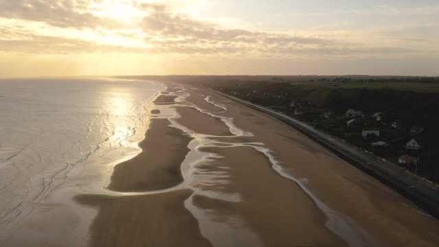 aerial flying high up over omaha beach in france at sunrise - normandie stock-videos und b-roll-filmmaterial