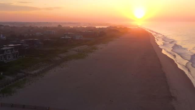 aerial flying left over beach and houses, bridgehampton, ny at sunrise - bridgehampton stock videos & royalty-free footage