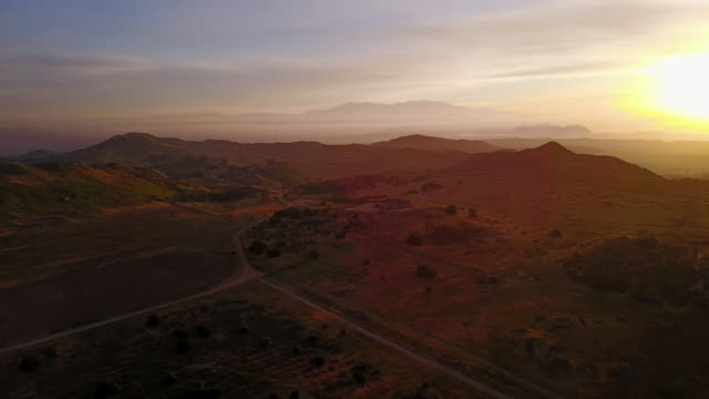 aerial flying left over southern california hilly area at sunrise - riverside california stock videos and b-roll footage