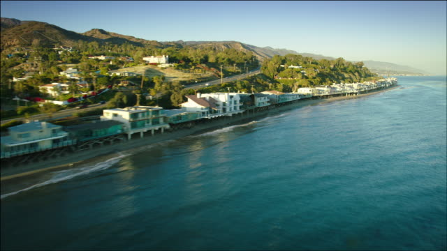 Aerial POV flying low along Pacific Ocean beachfront houses in Malibu, CA
