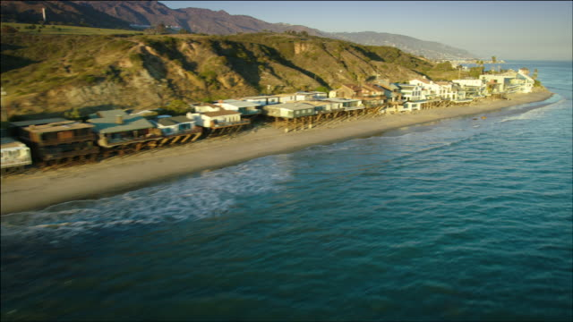 aerial pov flying low along pacific ocean beachfront houses in malibu, ca - malibu stock videos & royalty-free footage