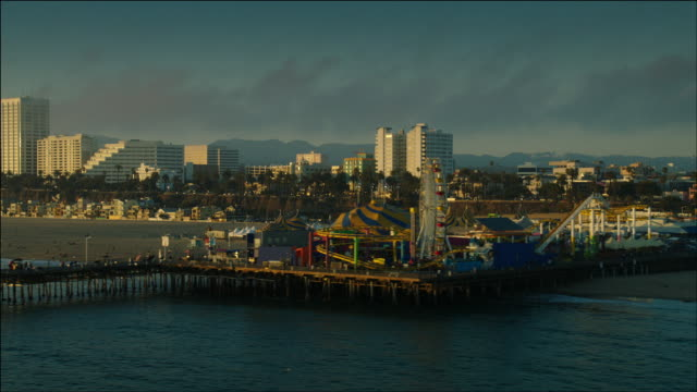 Aerial POV flying low along Pacific Ocean shoreline looking at the Santa Monica Pier, and the sunlight glinting off the highrise buildings in Santa Monica, CA, at Sunset