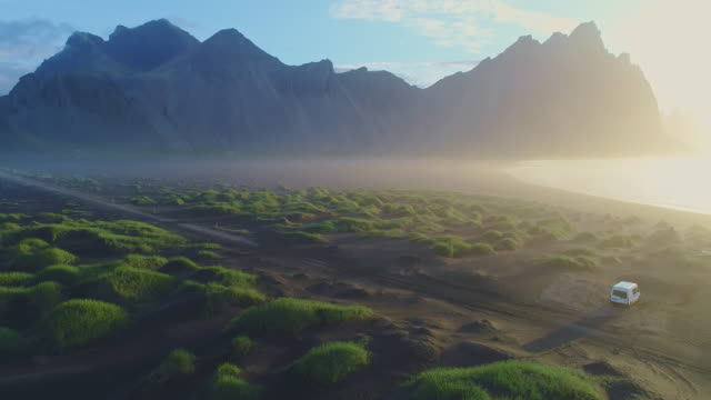 aerial flying low over black beach and sand dune in vestrahorn, iceland - atmosphere filter stock videos & royalty-free footage