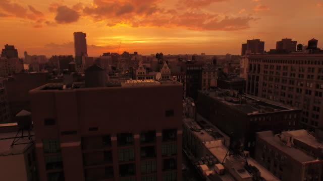 vídeos de stock, filmes e b-roll de aerial flying low over buildings at sunset in manhattan nyc - distrito da moda manhattan