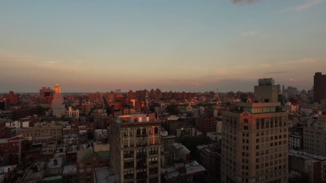 vídeos de stock, filmes e b-roll de aerial flying low over buildings at sunset in manhattan nyc - williamsburg new york