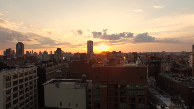 vidéos et rushes de aerial flying low over buildings at sunset in manhattan nyc - toit
