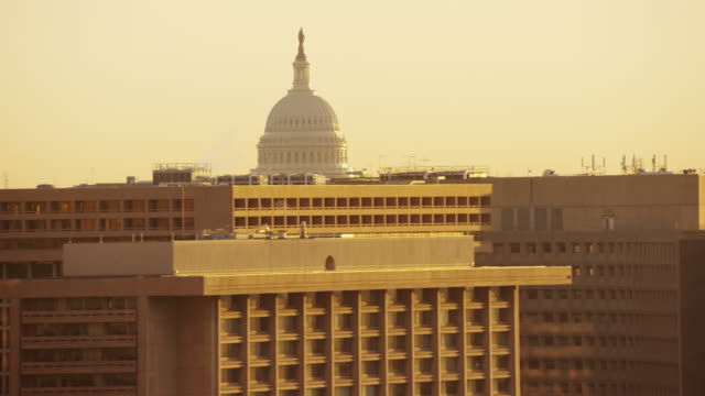 Aerial flying low over D.C. looking at United States Capitol, sunrise