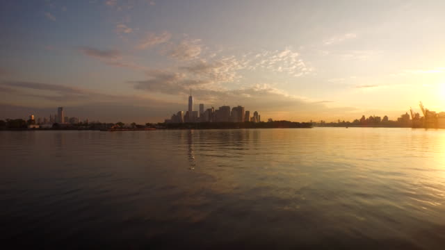 aerial flying low over east river towards manhattan at sunrise - east river stock videos & royalty-free footage