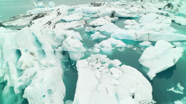 aerial flying low over jã¶kulsã¡rlã³n glacier lagoon in iceland - 氷河点の映像素材/bロール
