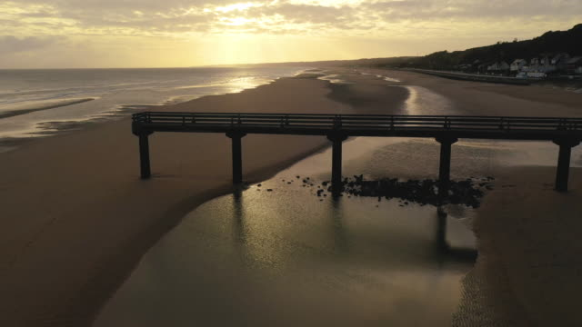 vidéos et rushes de aerial flying low over omaha beach back away from jetty in france at sunrise - cliff