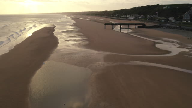 vidéos et rushes de aerial flying low over omaha beach full of seagull in france at sunrise - cliff
