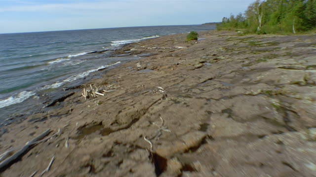 aerial flying low over rocky flats on coast of lake superior / over water / minnesota - lago superiore video stock e b–roll