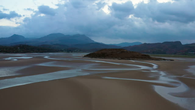 vídeos de stock e filmes b-roll de aerial flying low over sand in estuary at low tide in north wales at sunset - país de gales