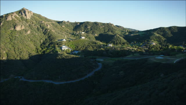 stockvideo's en b-roll-footage met aerial pov flying low over the santa monica mountains, seeing a few scattered houses, ca - malibu