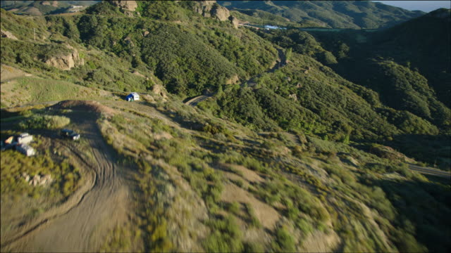 aerial pov flying low over the santa monica mountains, seeing a few scattered houses, motorhomes, tents, and campers, above malibu, ca - ventura stock videos and b-roll footage