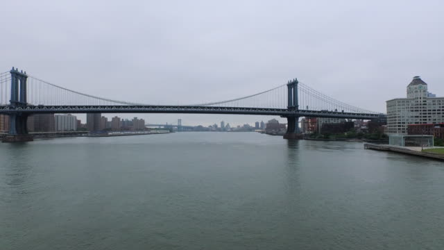 Aerial flying North under the Brooklyn then Manhattan Bridges on the East River, NYC
