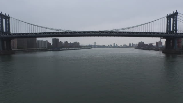 aerial flying north under the manhattan bridges on the east river, nyc - williamsburg bridge stock videos and b-roll footage