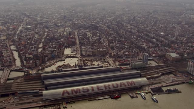 aerial flying over amsterdam train station - amsterdam stock videos & royalty-free footage