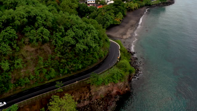 stockvideo's en b-roll-footage met aerial flying over and following road outside caribbean town of saint-pierre in martinique, daytime - french overseas territory