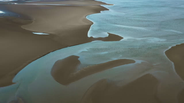 stockvideo's en b-roll-footage met aerial flying over and looking down at an estuary with rising tides, north wales, daytime - getijde