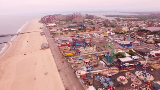 aerial flying over atlantic ocean, boardwalk, beach, and coney island in brooklyn, new york city - boardwalk stock videos & royalty-free footage