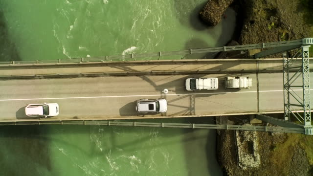 stockvideo's en b-roll-footage met aerial flying over bridge looking directly down at van pulling trailer in iceland - following moving activity