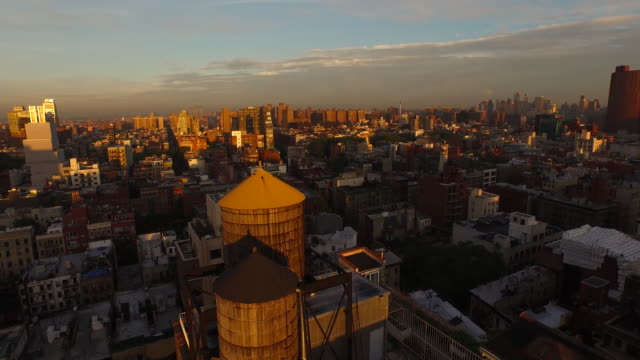 vídeos de stock, filmes e b-roll de aerial flying  over buildings at sunset in manhattan nyc - williamsburg new york