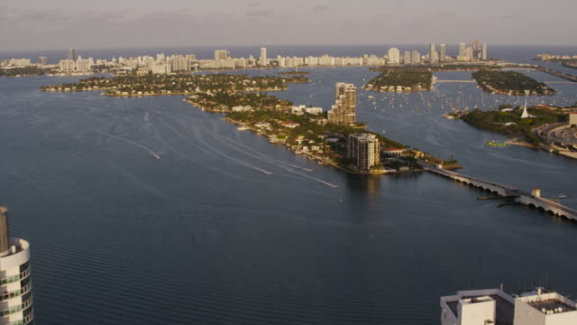 stockvideo's en b-roll-footage met aerial flying over buildings in downtown miami end of day, fl - macarthur causeway bridge