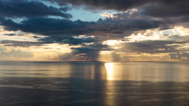 vidéos et rushes de aerial flying over caribbean sea looking at sun setting in the distance, sunset - french overseas territory