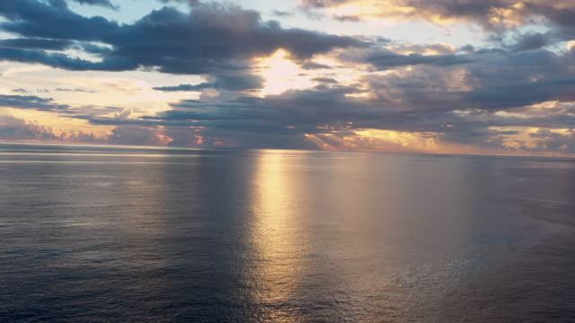 vídeos y material grabado en eventos de stock de aerial flying over caribbean sea looking at sun setting in the distance, sunset - territorios franceses de ultramar