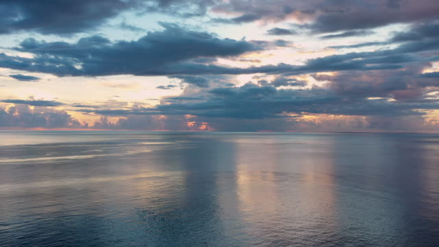 aerial flying over caribbean sea looking at sun setting in the distance, sunset - french overseas territory stock videos & royalty-free footage
