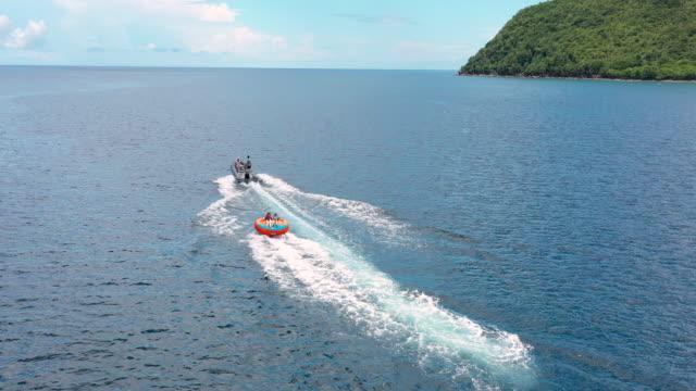stockvideo's en b-roll-footage met aerial flying over caribbean water looking down at people being pulled in inner tube - french overseas territory